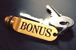 Bonus - Bunch of Keys with Text on Golden Keychain. Black Wooden Background. Closeup View with Selective Focus. 3D Illustration. Toned Image.
